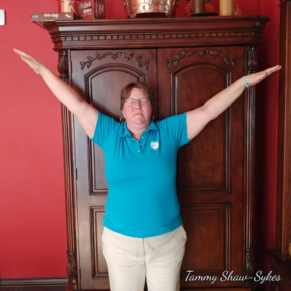 Tammy Shaw-Sykes standing in yoga pose with arms stretched over her head in front of wooden cabinet